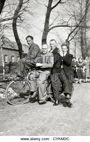 having fun posing with four on a bicycle rural Holland 1940s - Stock Photo