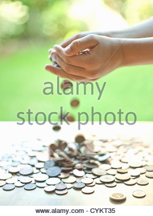 Hands pouring change on table - Stock Photo