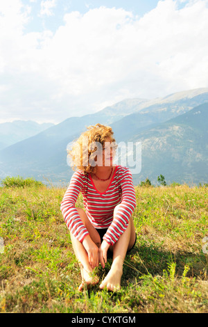 Woman sitting on rural hilltop - Stockfoto
