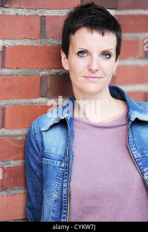 Woman leaning against brick wall - Stock Photo