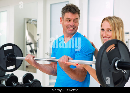 Trainer adjusting man's form in gym - Stock Photo