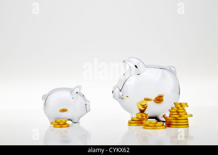 Stacks of gold coins by piggy banks - Stockfoto