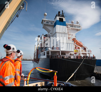Workers on tug boat overlooking ship - Stock Photo