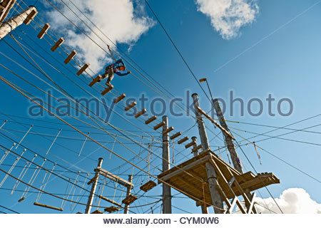 Boy walking on wooden rope bridge - Stock Photo