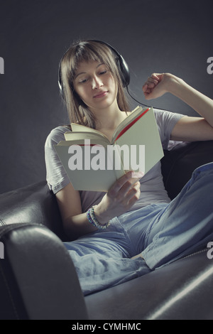 A young woman sits on a couch  reading a book and listening to music through a pair of headphones - Stock Photo