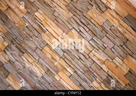 An angled narrow brick facade provides an abstract pattern of colors and shapes to an outdoor wall in Cotacachi, - Stockfoto