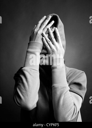 young woman hide her face in her hands - Stock Photo