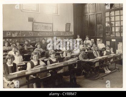 Vintage school photograph of junior girls in a classroom sitting at their desks with open books, circa 1925 - Stock Photo