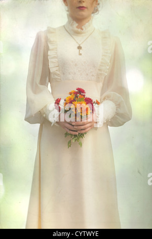 a woman in a victorian dress on a meadow with a bouquet of flowers - Stock Photo