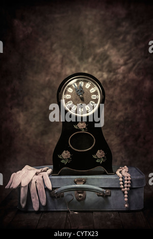 an old table clock in Biedermeier style with a leather suitcase, gloves and a pearl necklace - Stock Photo