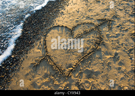 A heart with an arrow drawn in sand on a beach - Stockfoto