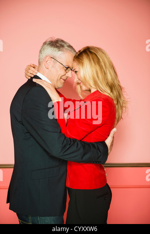 Germany, Stuttgart, Business couple embracing in apartment, close up - Stock Photo