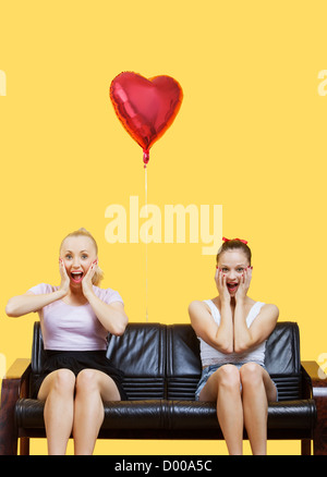 Portrait of two amazed young women sitting on sofa with heart shaped balloon over yellow background - Stockfoto