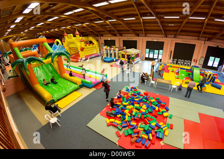 Inflatable structures (bouncy castle type) for kids in an indoor funfair. - Stock Photo
