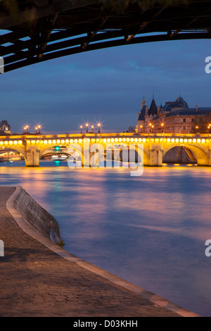 Twilight along River Seine with Pont Neuf and the Conciergerie, Paris France - Stock Photo
