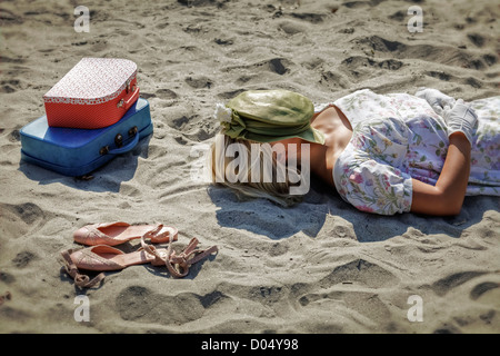 a woman in a floral dress is lying on a beach next to her shoes and two vintage suitcases - Stock Photo