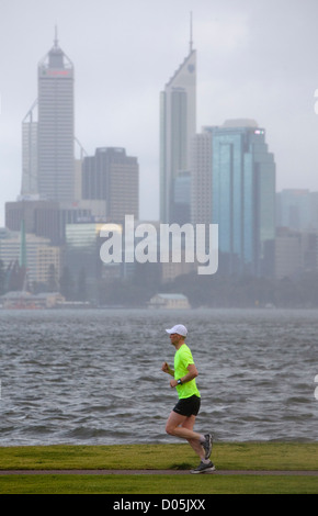 A man jogging in the rain with a river and city in the background. - Stock Photo
