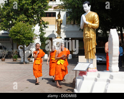 Young monks in the courtyard of the Wat Phra Singha temple, Chiang Rai, Thailand, Asia - Stock Photo