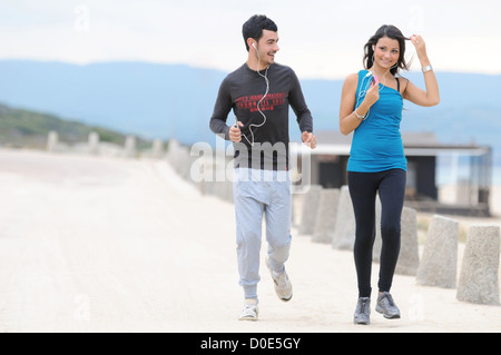 Young couple running and jogging on beach - Stock Photo