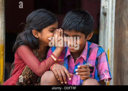 Young Indian girl whispering to a boy outside their rural Indian viilage home. Andhra Pradesh, India - Stock Photo