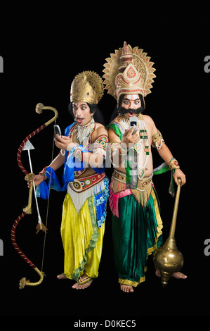 Two men dressed-up as Rama and Ravana and reading text message - Stock Photo