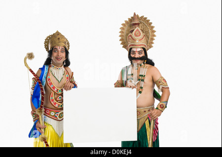 Two men dressed-up as Rama and Ravana and holding a blank placard - Stock Photo