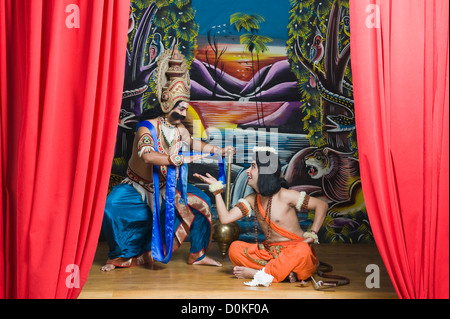 Two men dressed-up as Rama and Ravana giving high-five to each other - Stock Photo