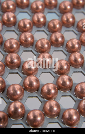 little metallic balls in metallic honeycomb pattern - Stock Photo