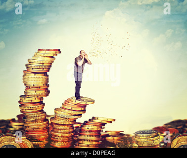man on coin piles speak about money - Stock Photo