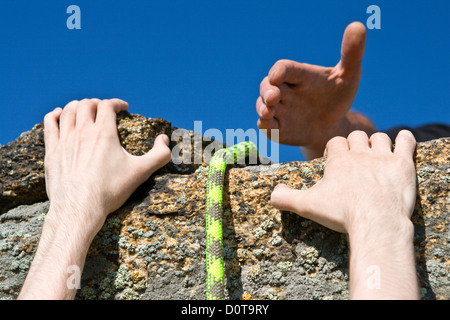 Rock climber reaching for helping-hand partner. - Stockfoto