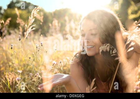 Teenage girl lying in field, close up - Stock Photo