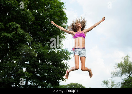 Girl on trampoline - Stock Photo