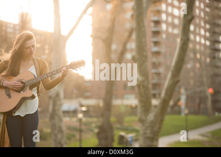 Young woman playing guitar in the park - Stock Photo