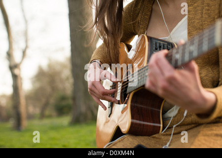 Young woman playing guitar outdoors - Stock Photo