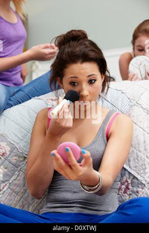 Girl applying makeup in bedroom - Stock Photo