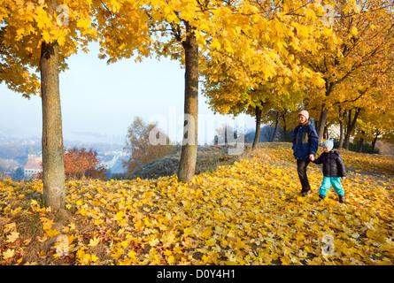 Family in autumn maple park - Stock Photo
