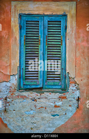 worn old window with blue shutters on a broken old stucco wall in rural Spain - Stock Photo