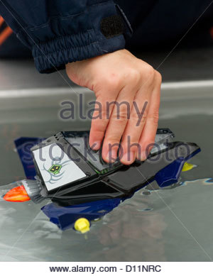 boy child children playing toy boat cold weather wet water hand - Stock Photo