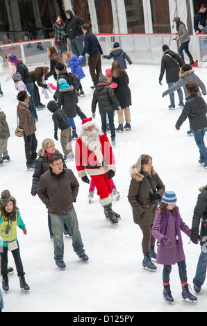 Santa Claus seen skating on the ice rink at the Rockefeller Center New York USA - Stock Photo
