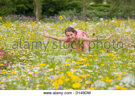 Father holding flying among wildflowers in sunny meadow - Stockfoto