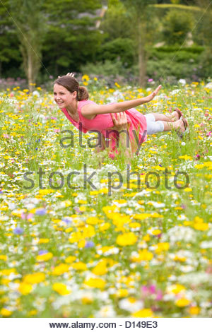 Father holding flying girl among wildflowers in sunny meadow - Stockfoto