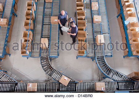 Workers meeting among boxes on conveyor belts in distribution warehouse - Stock Photo