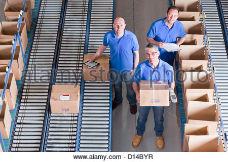 Portrait of smiling workers packing boxes on conveyor belts in distribution warehouse - Stock Photo