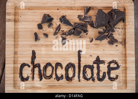 Chocolate written on cutting board - Stock Photo