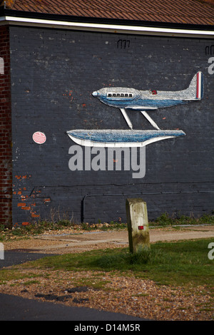 Supermarine S.6B decorative plane made of sea shells on side of building at Calshot, Hampshire in November - Stock Photo