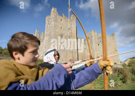 Students in period dress shooting arrows - Stock Photo