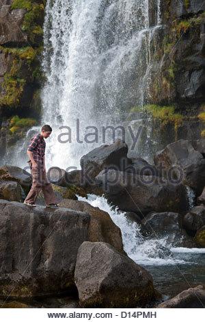 Boy climbing rocks by waterfall - Stock Photo