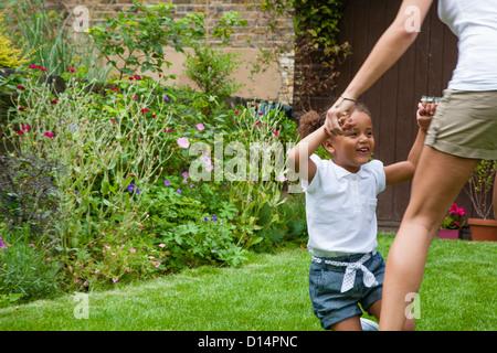 Mother and daughter dancing in garden - Stock Photo