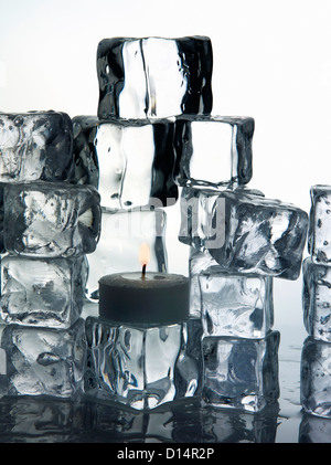 Stacks of ice cubes and candle - Stock Photo