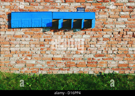 Aged brick construction wall with old post boxes. - Stock Photo